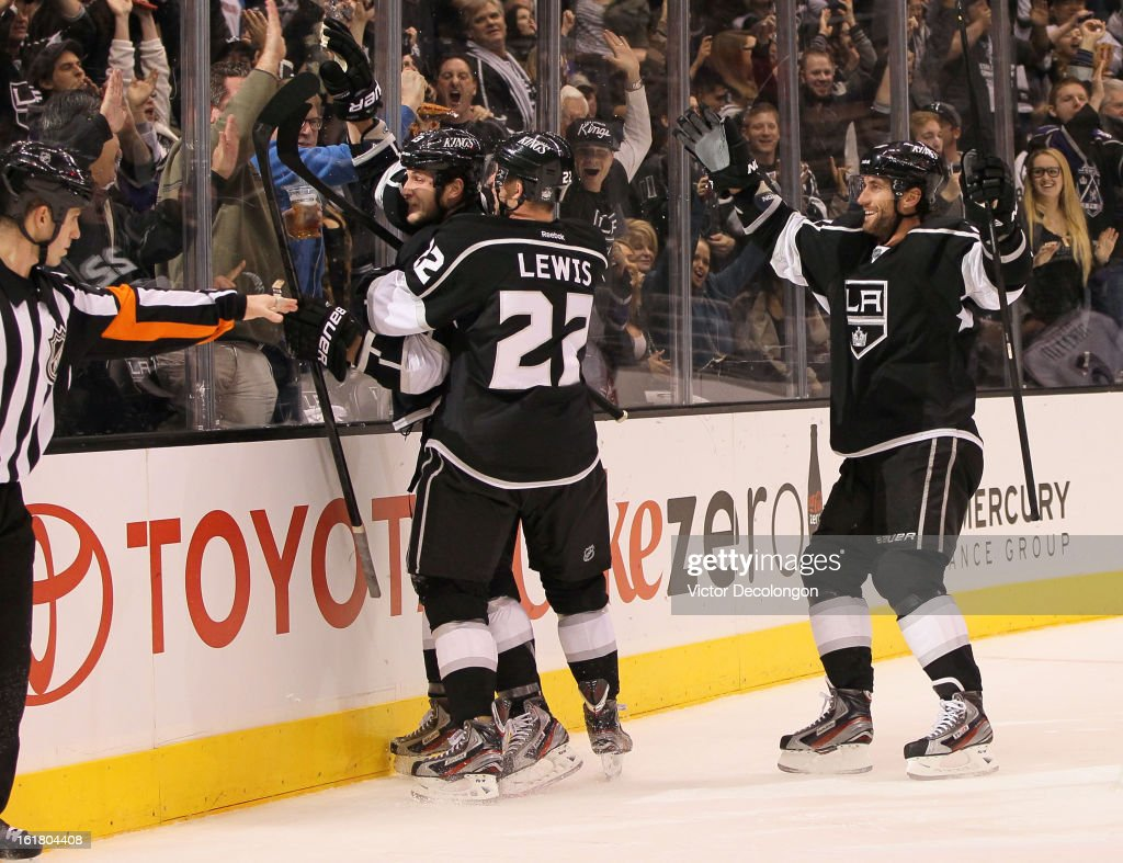 Trevor Lewis #22 and Jarret Stoll #28 of the Los Angeles Kings celebrate with teammate Kyle Clifford #13 after Clifford's goal in the second period against Columbus Blue Jackets during the NHL game at Staples Center on February 15, 2013 in Los Angeles, California. The Kings defeated the Blue Jackets 2-1.