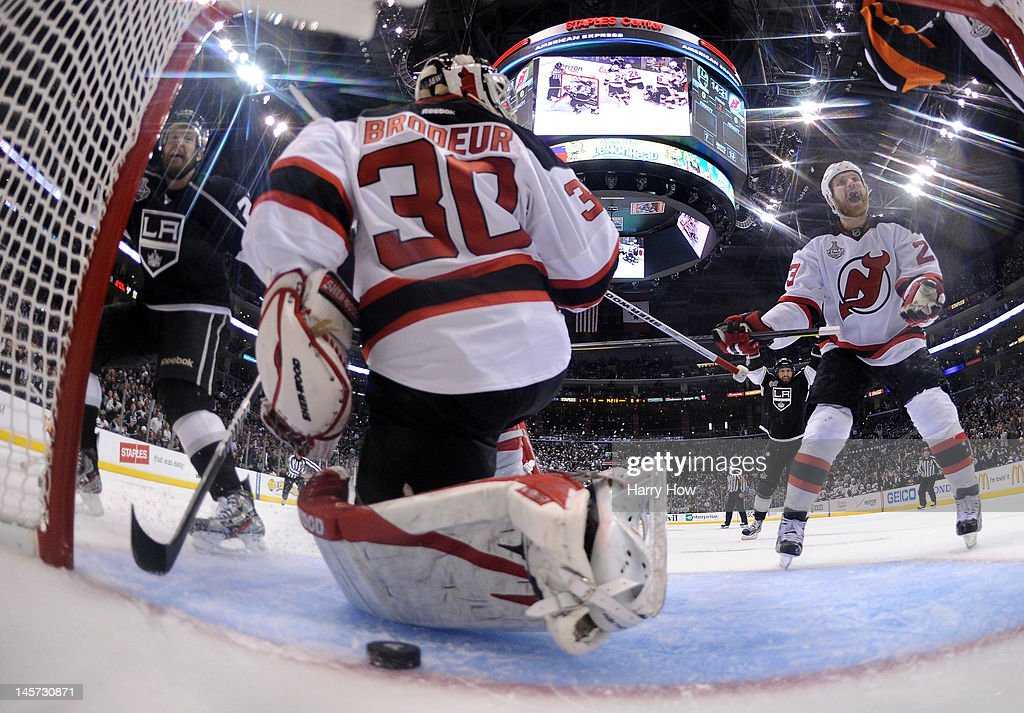 Trevor Lewis of the Los Angeles Kings and David Clarkson of the New Jersey Devils react after the puck goes into the net for a goal in Game Three of...