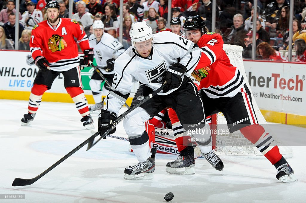 Trevor Lewis #22 of the Los Angeles Kings and Duncan Keith #2 of the Chicago Blackhawks battle for the puck during the NHL game on March 25, 2013 at the United Center in Chicago, Illinois.