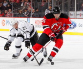 Trevor Lewis of the Los Angeles Kings checks Adam Larsson of the New Jersey Devils in an NHL hockey game at Prudential Center on November 15 2013 in...