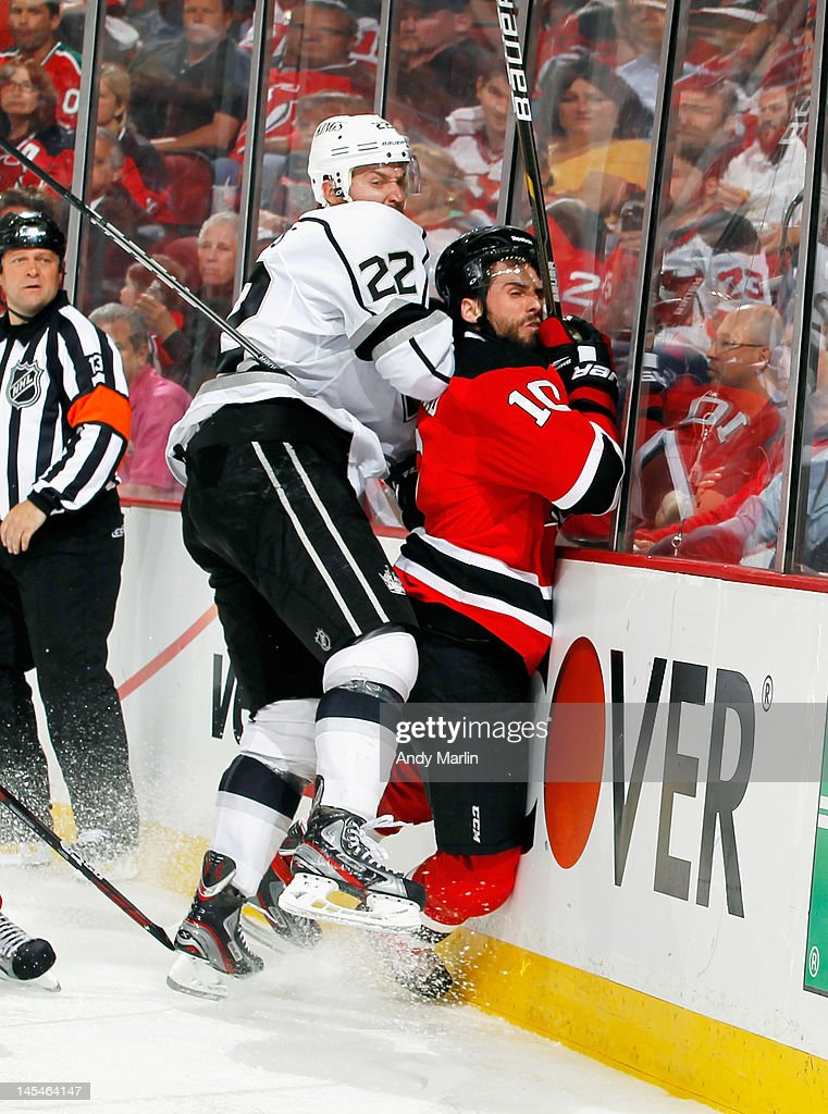 Trevor Lewis of the Los Angeles Kings checks Peter Harrold of the New Jersey Devils into the boards in Game One of the 2012 NHL Stanley Cup Final at...