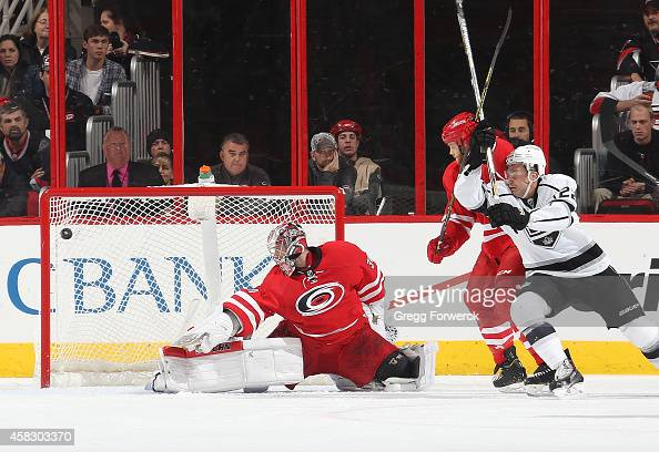 Trevor Lewis of the Los Angeles Kings creates traffic as Alec Martinez fires a shot past Cam Ward of the Carolina Hurricanes during their NHL game at...