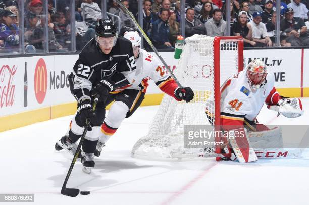 Trevor Lewis of the Los Angeles Kings handles the puck against Travis Hamonic and Mike Smith of the Calgary Flames at STAPLES Center on October 11...