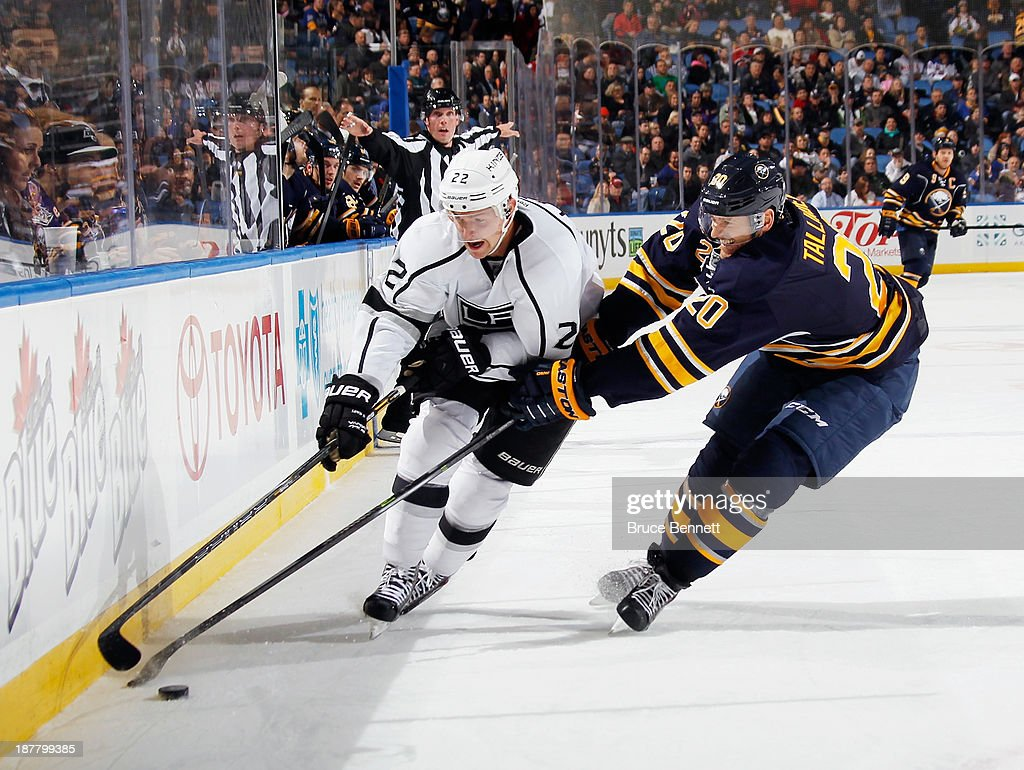 Trevor Lewis #22 of the Los Angeles Kings moves the puck around Henrik Tallinder #20 of the Buffalo Sabres at the First Niagara Center on November 12, 2013 in Buffalo, New York.