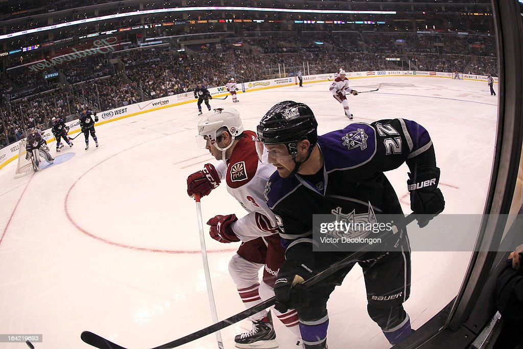 Trevor Lewis #22 of the Los Angeles Kings plays the puck along the corner boards past Keith Yandle #3 of the Phoenix Coyotes during the NHL game at Staples Center on March 18, 2013 in Los Angeles, California. The Kings defeated the Coyotes 4-0.