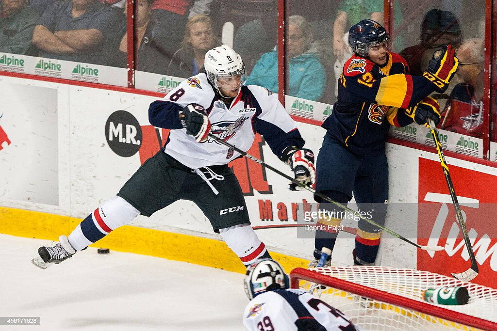 Trevor Murphy #8 of the Windsor Spitfires places a huge hit on Alex DeBrincat of the Erie Otters on September 26, 2014 at the WFCU Centre in Windsor, Ontario, Canada.
