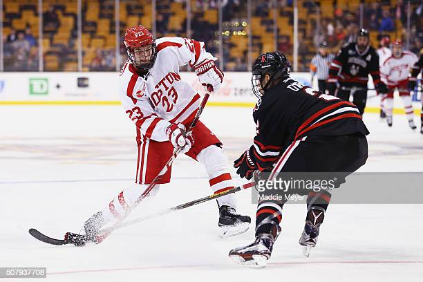 Trevor Owens of the Northeastern Huskies defends a shot from Jakob Forsbacka Karlsson of the Boston University Terriers during the third period at TD...