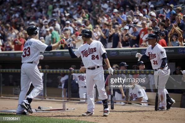 Trevor Plouffe and Oswaldo Arcia of the Minnesota Twins congratulate Justin Morneau on scoring against the Kansas City Royals during the game on June...