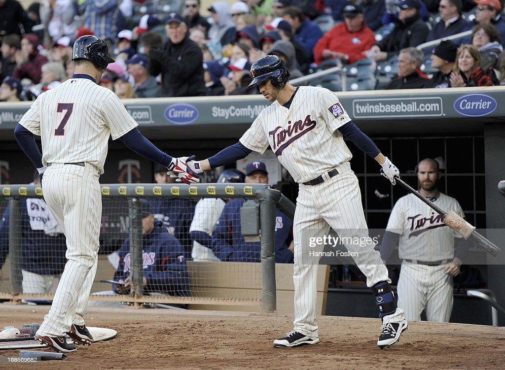 Trevor Plouffe #24 of the Minnesota Twins congratulates teammate Joe Mauer #7 on scoring against the Baltimore Orioles during the third inning of the game on May 11, 2013 at Target Field in Minneapolis, Minnesota.
