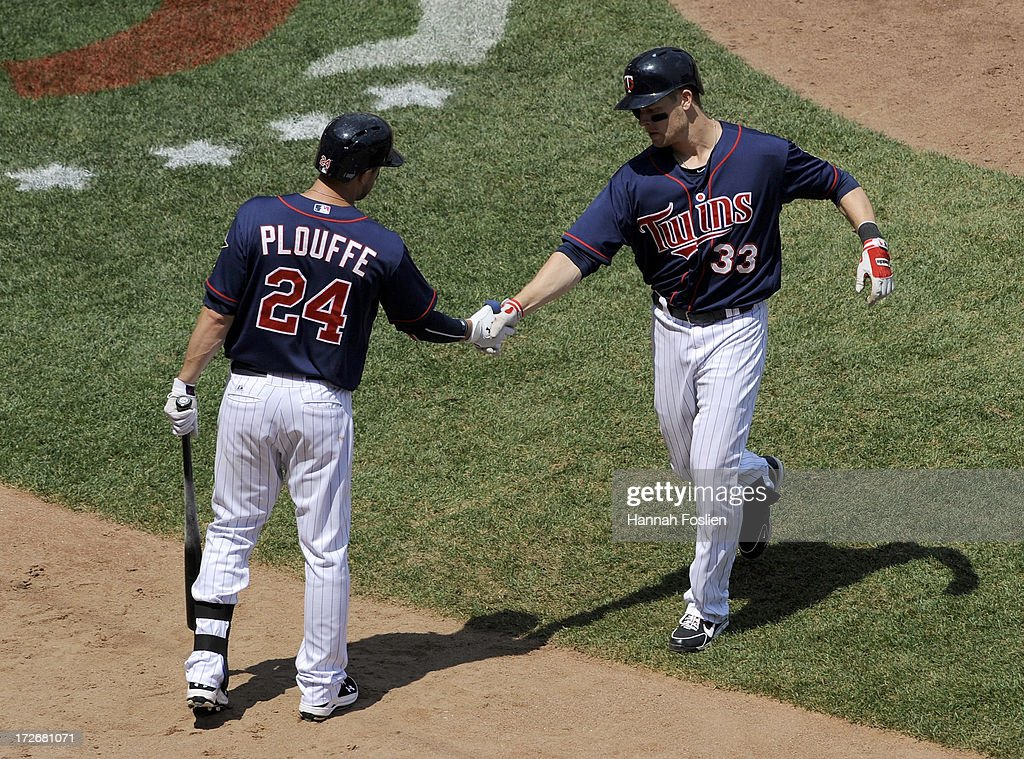 Trevor Plouffe #24 of the Minnesota Twins congratulates teammate Justin Morneau #33 on a solo home run against the New York Yankees during the fourth inning of the game on July 4, 2013 at Target Field in Minneapolis, Minnesota.