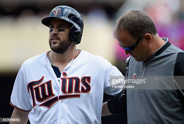 Trevor Plouffe of the Minnesota Twins is helped off the field by trainer Dave Pruemer after being out at first base during the sixth inning of the...