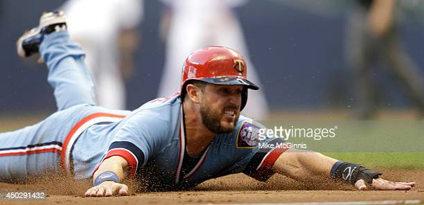 Trevor Plouffe of the Minnesota Twins slides into third base after an errand throw to second base during the top of the second inning against the...
