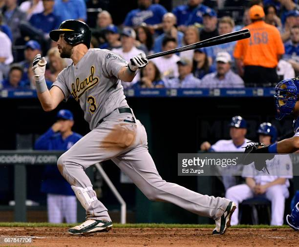 Trevor Plouffe of the Oakland Athletics hits a sacrifice fly in the fourth inning against the Kansas City Royals at Kauffman Stadium on April 12 2017...