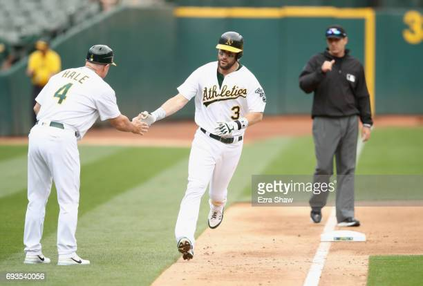 Trevor Plouffe of the Oakland Athletics is congratulated by third base coach Chip Hale after he hit a home run in the fourth inning against the...
