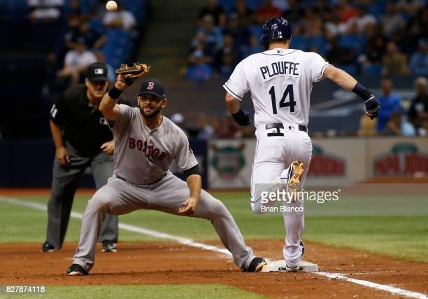 Trevor Plouffe of the Tampa Bay Rays gets to first base ahead of first baseman Mitch Moreland of the Boston Red Sox to reach on the throwing error by...
