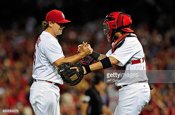 Trevor Rosenthal of the St Louis Cardinals celebrates with Yadier Molina after defeating the Washington Nationals at Busch Stadium on June 13 2014 in...