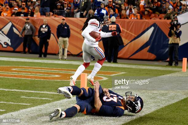 Trevor Siemian of the Denver Broncos dives and misses Janoris Jenkins of the New York Giants as he scores a touchdown on an interception thrown by...