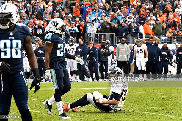 Trevor Siemian of the Denver Broncos looks up at Daimion Stafford of the Tennessee Titans after a push that slid him through the backfield at Nissan...