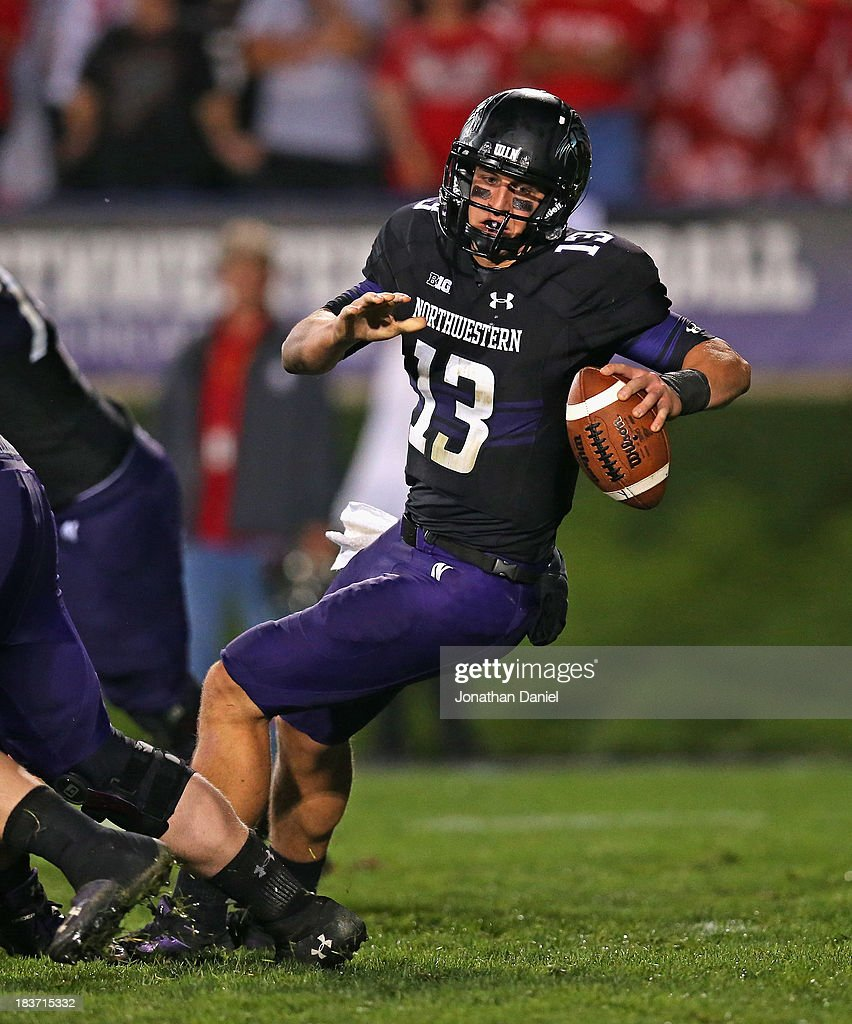 Trevor Siemian #13 of the Northwestern Wildcats falls after the snap against the Ohio State Buckeyes at Ryan Field on October 5, 2013 in Evanston, Illinois. Ohio State defeated Northwestern 40-30.