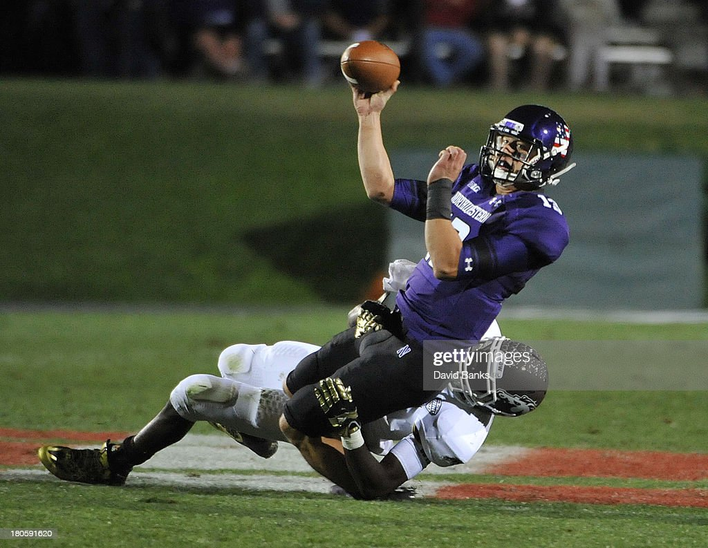 Trevor Siemian #13 of the Northwestern Wildcats is pressured by Edward Rolle #4 of the Western Michigan Broncos during the second quarter on September 14, 2013 at Ryan Field in Evanston, Illinois.