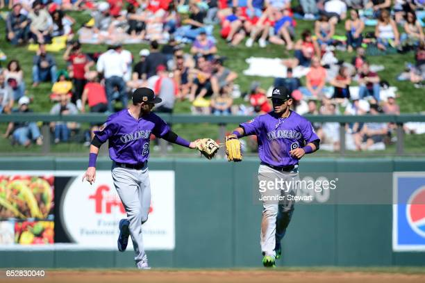 Trevor Story and Gerardo Parra of the Colorado Rockies high five during the spring training game against the Arizona Diamondbacks at Salt River...
