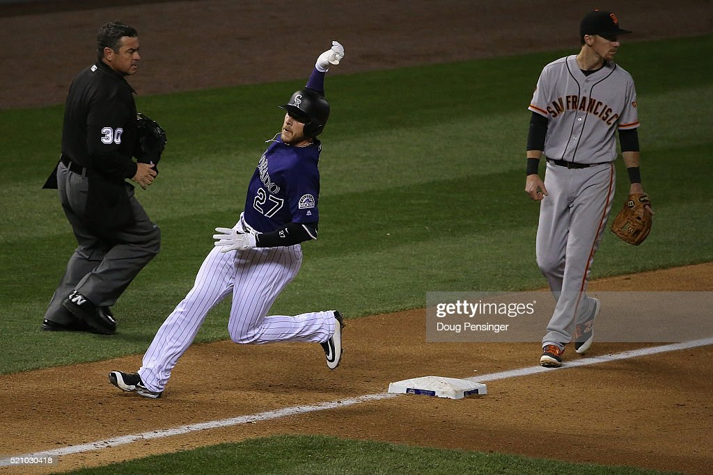 Trevor Story of the Colorado Rockies arrives at third with a triple off of Cory Gearrin of the San Francisco Giants as third baseman Matt Duffy of...