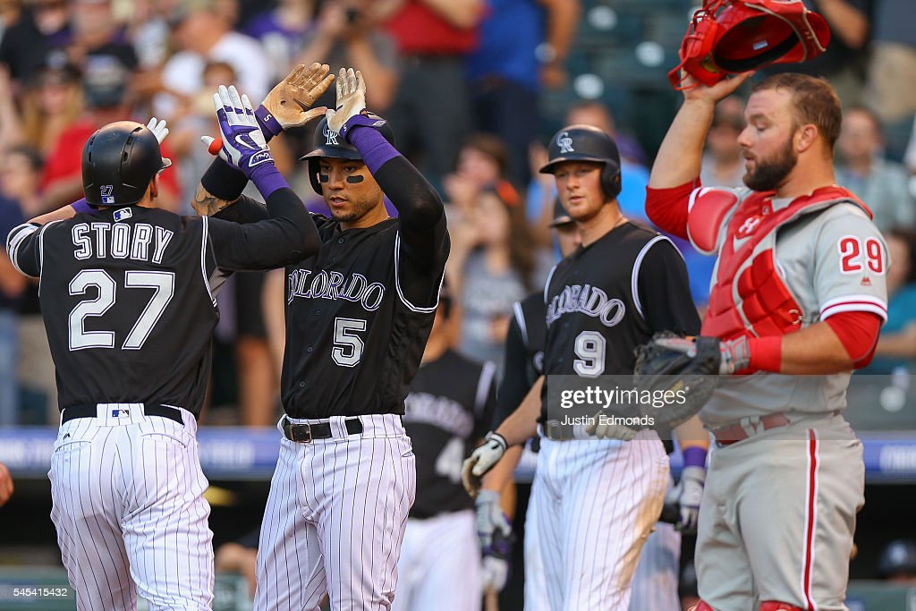 Trevor Story of the Colorado Rockies celebrates his three run home run with Carlos Gonzalez and DJ LeMahieu as Cameron Rupp of the Philadelphia...