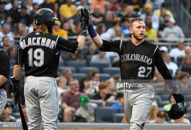 Trevor Story of the Colorado Rockies high fives with Charlie Blackmon after scoring on an RBI single by Tony Wolters in the fifth inning during the...