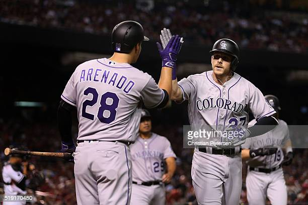 Trevor Story of the Colorado Rockies highfives Nolan Arenado after Story hit a threerun home run against the Arizona Diamondbacks during the third...