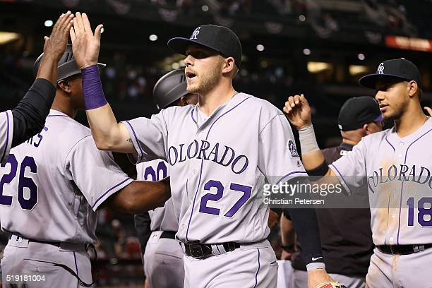 Trevor Story of the Colorado Rockies highfives teammates after defeating the Arizona Diamondbacks 105 in the MLB opening day game at Chase Field on...