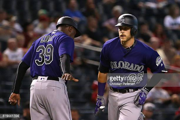 Trevor Story of the Colorado Rockies highfives third base coach Stu Cole after hitting a tworun home run against the Arizona Diamondbacks during the...