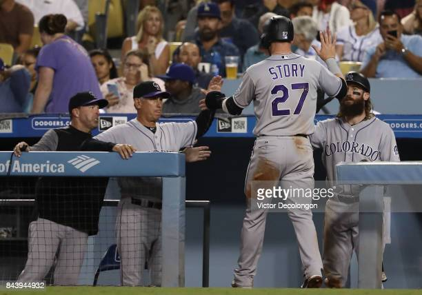 Trevor Story of the Colorado Rockies is congratulated by manager Bud Black and Charlie Blackmon of the Colorado Rockies after Story scored in the...
