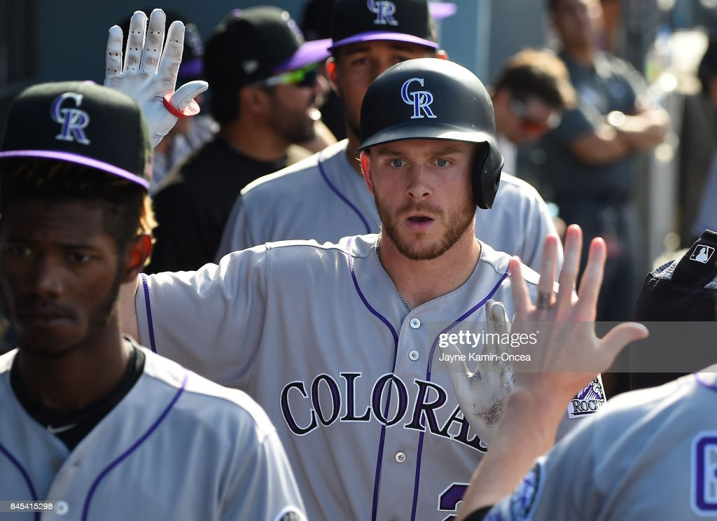 Trevor Story #27 of the Colorado Rockies is greeted in the dugout after a solo home run in the ninth inning of the game against the Los Angeles Dodgers at Dodger Stadium on September 10, 2017 in Los Angeles, California.