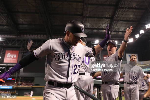 Trevor Story of the Colorado Rockies reacts with bench coach Mike Redmond after hitting a solo home run during the top of the eighth inning of the...