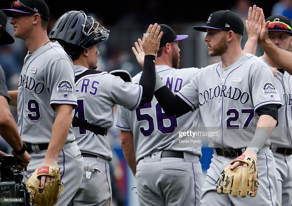 Trevor Story #27 of the Colorado Rockies, right, high fives Tony Wolters #14 after beating the San Diego Padres 3-1 in a baseball game at PETCO Park on June 4, 2017 in San Diego, California.