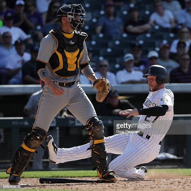 Trevor Story of the Colorado Rockies slides home to score behind catcher Chris Stewart of the Pittsburgh Pirates on a sacrifice bunt by Jorge De La...