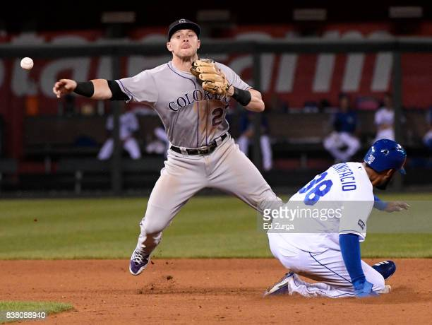 Trevor Story of the Colorado Rockies throws to first past Jorge Bonifacio of the Kansas City Royals as he tries to complete a double play in the...