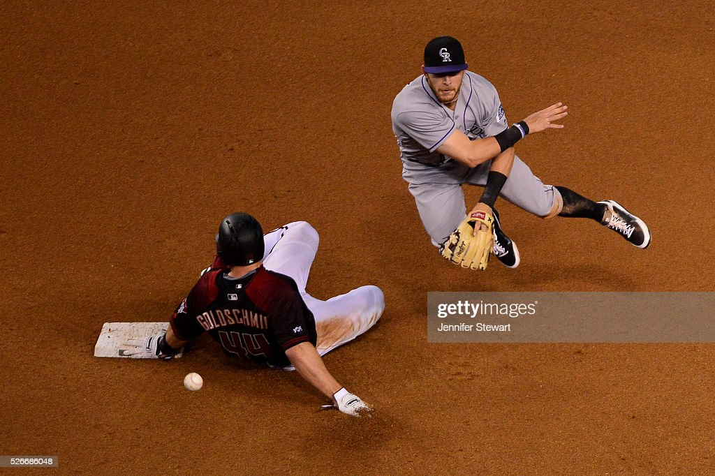 Trevor Story of the Colorado Rockies turns the double play over the sliding Paul Goldschmidt of the Arizona Diamondbacks in the fourth inning at...