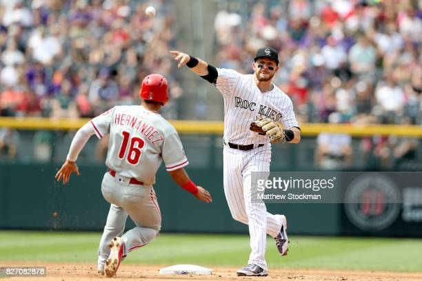 Trevor Story of the Colorado Rockies turns the first half of a double play against Cesar Hernandez of the Philadelphia Phillies in the sixth inning...