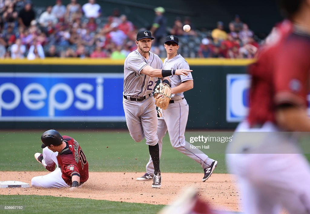 Trevor Story #27 of the Colorado Rockies unsuccessfully attempts to turn a double play as Chris Herrmann #10 of the Arizona Diamondbacks is forced out while sliding into second base during the sixth inning at Chase Field on May 01, 2016 in Phoenix, Arizona.