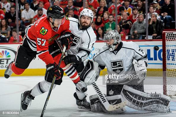 Trevor van Riemsdyk of the Chicago Blackhawks and Drew Doughty of the Los Angeles Kings get physical as the puck flys past goalie Jonathan Quick in...