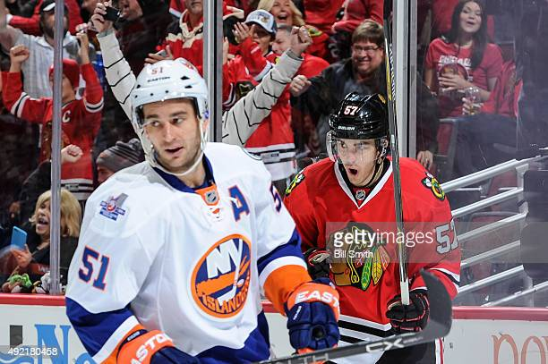 Trevor van Riemsdyk of the Chicago Blackhawks celebrates behind Frans Nielsen of the New York Islanders after scoring his first career NHL goal in...