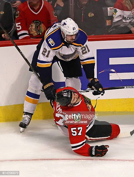 Trevor van Riemsdyk of the Chicago Blackhawks hits the ice after a high stick from Patrik Berglund of the St Louis Blues during the season opening...