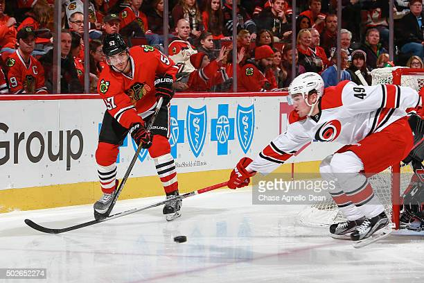Trevor van Riemsdyk of the Chicago Blackhawks hits the puck past Victor Rask of the Carolina Hurricanes in the first period of the NHL game at the...