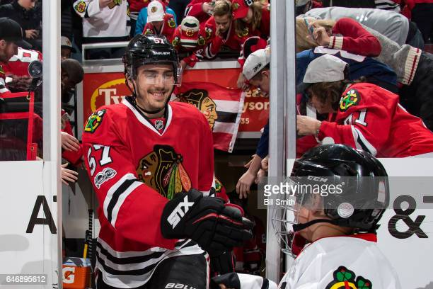 Trevor van Riemsdyk of the Chicago Blackhawks interacts with a young fan prior to the game against the Pittsburgh Penguins at the United Center on...