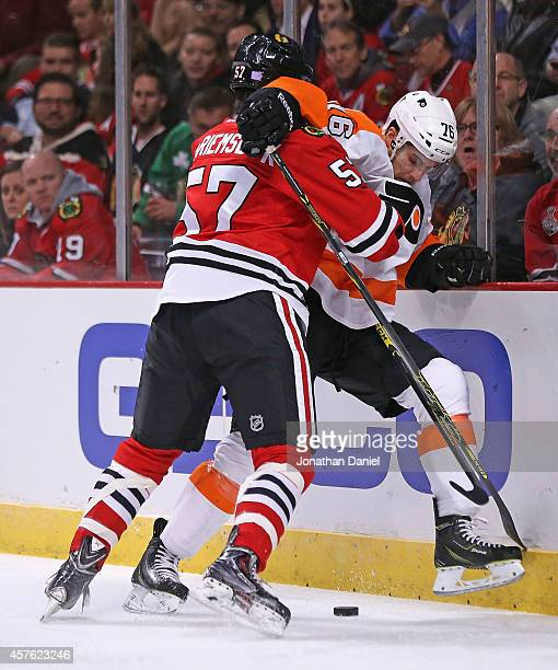 Trevor van Riemsdyk of the Chicago Blackhawks pins Chris Vande Velde of the Philadelphia Flyers at boards as they battle for the puck at the United...