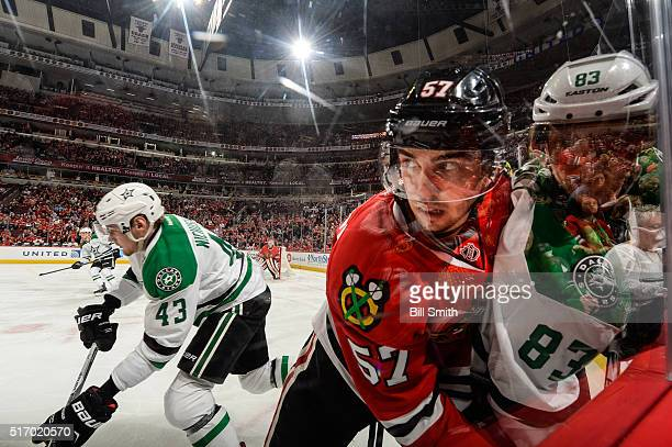 Trevor van Riemsdyk of the Chicago Blackhawks pushes Ales Hemsky of the Dallas Stars into the glass as Valeri Nichushkin skates in the background in...