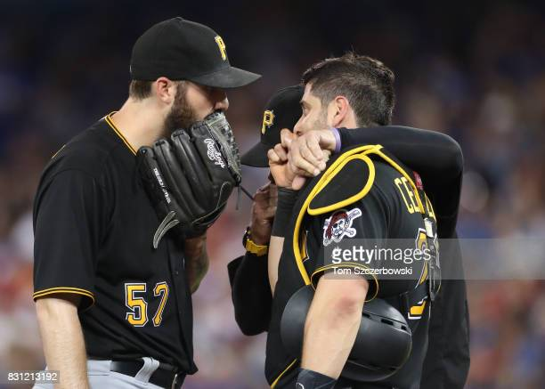 Trevor Williams of the Pittsburgh Pirates listens to pitching coach Ray Searage as Francisco Cervelli listens in on the mound in the fifth inning...