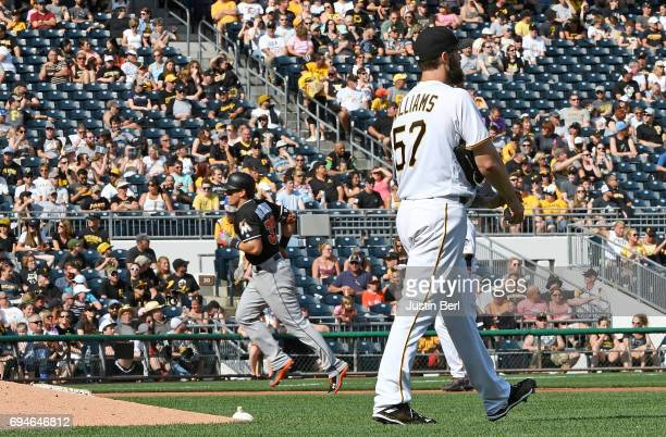 Trevor Williams of the Pittsburgh Pirates reacts as Derek Dietrich of the Miami Marlins rounds the bases after hitting a solo home run in the fourth...
