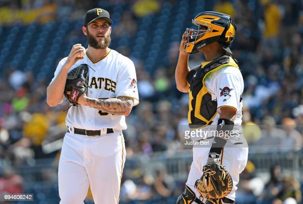 Trevor Williams of the Pittsburgh Pirates talks with Elias Diaz after giving up a two run double to Marcell Ozuna of the Miami Marlins in the first...